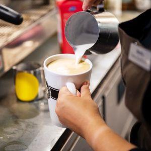 barista kaataa latteen maitoa