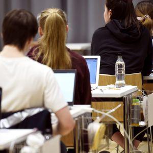 Yo-kokelaita ja kannettavia tietokoneita juuri ennen ylioppilaskirjoituksien äidinkielen lukutaidon kokeen alkua Ressun lukiossa Helsingissä 10. maaliskuuta.