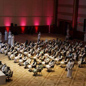 Kuvassa talebanit istuvat suuressa salissa Dohassa.