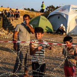 ihmisiä alkeellisessa leirissä