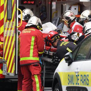 Palomiehet siirtävät puukotuksessa loukkaantunutta ambulanssiin Pariisissa.