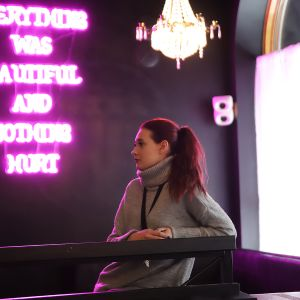"""Turkulaisen yökerho Studion ravintolapäällikkö Jasmin Kettunen, taustalla neonvaloissa teksti """"Everything was beautiful and nothing hurt"""""""