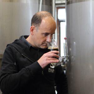 Darron Anley nuuhkaisee olutta lasissa.