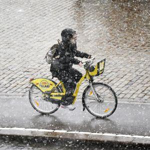 Nainen pyöräilee kaupunkipyörällä lumisateessa Helsingissä.