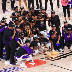 Los Angeles Lakersin pelaajat poseeraavat mestaruuspystin kanssa.