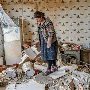 Nainen tutkii yhteenotossa tuhoutunutta kotiaan Azerbaidžanin Terterissä.