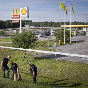 Kolme poliisia ruohikkoisessa rinteessä, taustalla bensa-asema.