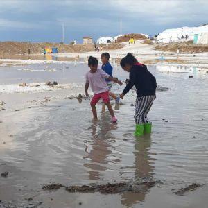 lapset leikkivät lätäkössä