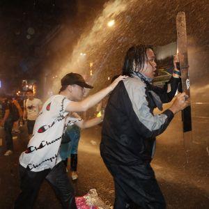 Mielenosoittajia ammuttiin vesitykeillä Bangkokissa perjantaina.