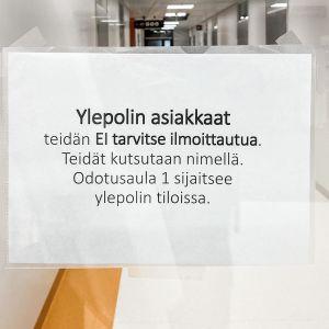 Lasiovessa oleva tiedote asiakkaille sairaalassa asioinnista.