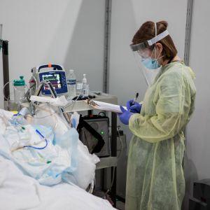 Suoja-asuinen lääkäri tekee muistiinpanoja hengityskoneessa olevan potilaan vuoteen ääressä.