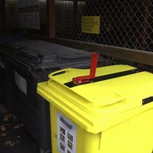 Nainen pudottaa kaksi muovipussia keltaiseen muovinkeräysastiaan.