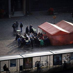Ihmisiä torikahvilassa Hakaniemen torilla.
