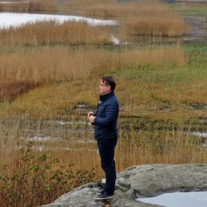 Kiikaria pitelevä mies kalliolla. Ympärillä syksyn kellastuttamaa rantaruovikkoa.