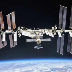 Avaruusasema aurinkopaneelisiipineen. Alla näkyy Maan kaareva, pilvien peittämä pinta.