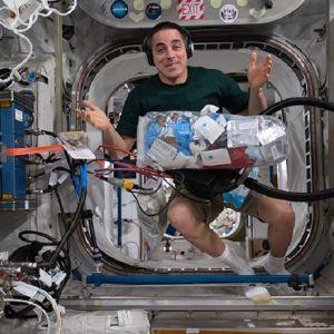 Shortseihin pukeutunut mies leijuu avaruusasemalla. Edessään hänellä on iso muovipussi täynnä roskia.