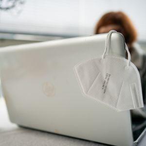 Nainen työskentelee kannettavalla tietokonella, koneen näytön kulmalla roikkuu kasvomaski.