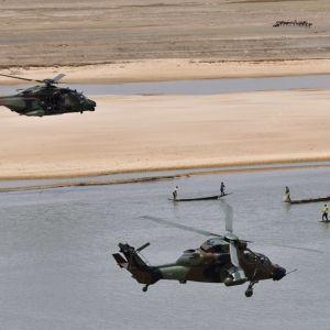 kaksi helikopterian lentää joen yllä