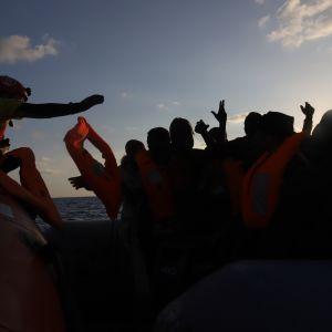 Open Armsin pelastajat jakoivat tulijoille pelastusliivejä. Kapteeni Marc Reigin mukaan salakuljettajat lähettävät siirtolaiset matkaan tietäen, että ne eivät koskaan pääse perille. Veneet eivät kestä pitkää merimatkaa eikä niissä usein ole edes polttoainetta tarpeeksi.
