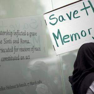 """Mielenosoittaja pitelee pahvilaatikosta tehtyä kylttiä, jossa lukee englanniksi """"pelastakaa muisto"""". Taustalla näkyy muistomerkin teksti, jossa liittokansleri Helmut Kohl tunnustaa romanien kansanmurhan."""