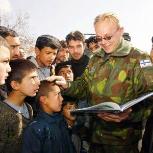 Suomalainen ISAF-kriisinhallintajoukkojen sotilas näyttää Kabulissa paikallisille opiskelijoille kirjaa Suomesta.