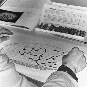 Mies piirtää väriliiduilla