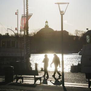 Kaupungin siluetti, tummia hahmoja etualalla.