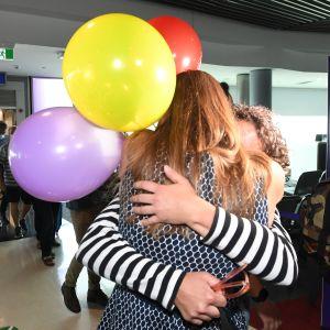 Matkustaja halaa läheistään Brisbanen lentokentällä 1. joulukuuta 2020. Ensimmäinen lento Melbournesta Bristabeen saapui sen jälkeen, kun Queensland avasi rajansa kuukausien sulun päätyttyä.