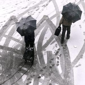 Jalankulkijoita lumisella kadulla.