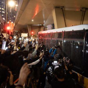 Demokratia-aktivisteja kuljettava pikkubussi tukea osoittavien mielenosoittajien ympäröimänä oikeustalolla 2. joulukuuta.