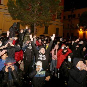 Huutavia mielenosoittajia ulkona, joillakin on kasvoilla maski.