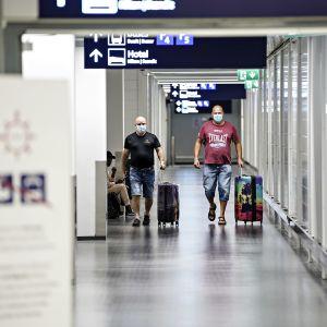 Kaksi matkustajaa kävelee matkatavaroidensa kanssa Helsinki-Vantaan lentoasemalla.