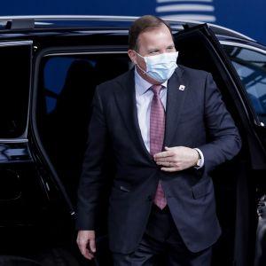 Löfven avoin autonovi takanaan, päällä puku, kasvoilla maski.