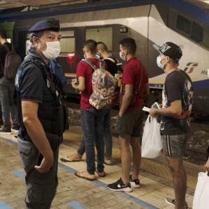 Poliisi valvoo ihmisiä rautatieasemalla.
