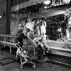 Mustavalkoinen kuva vuodelta 1993 näyttää lapset ihailemassa Stockmannin jouluikkunaa.