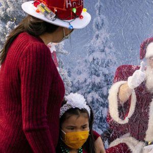 Joulupukki näyttää peukkua tytölle ja äidille.