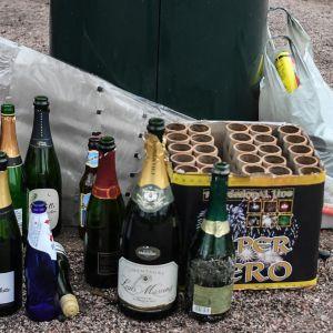 Tyhjiä alkoholipulloja ja käytettyjen ilotulitteiden pakkauksia.