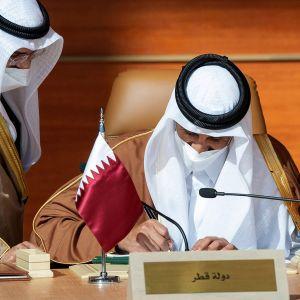 Qatarin sheikki Tamim bin Hamad Al-Thani allekirjoittaa sopimusta.