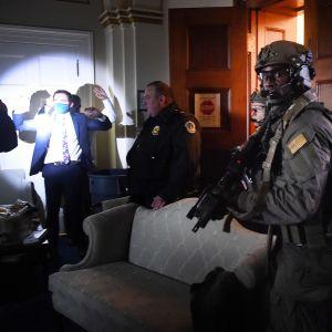 Poliisi tarkastaa tiloja, kun kongressin henkilökunta odottaa kädet ylhäällä.