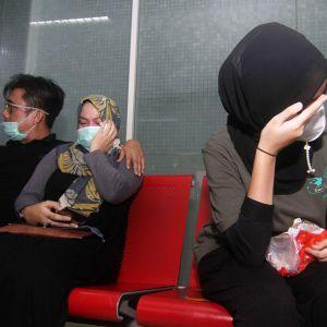 Kadonneiden matkustajien omaiset itkevät lentokentällä.
