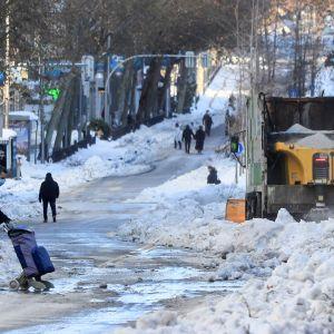 Mies ylitää lumista katua Madridissa.