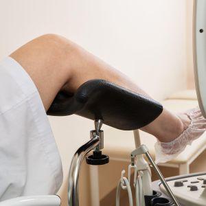 Henkilön jalat gynekologin tuolissa.