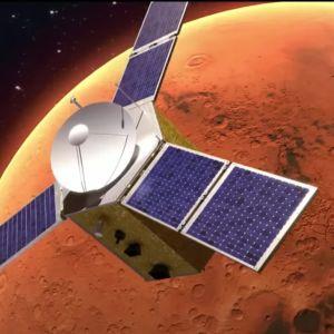Piirroskuva luotaimesta, jolla on kolme sinistä aurinkopaneelisiipeä. Taustalla oranssinpunainen Mars.