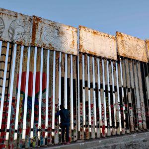 Mies katsoo Yhdysvaltain ja Meksikon rajalle pystytetyn muurin raosta Meksikon Tijuanan puolelta 16. tammikuuta 2021.