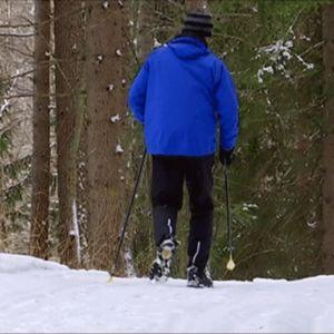 mies sauvakävelee lumisella tiellä