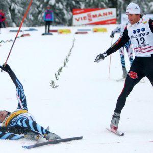 Kohta osuu! Voittajana maalinjan ylittänyt Hannu Manninen lyyhistyneenä lumen pintaan Lillehammerin sprintin jälkeen. Vieressä Ronny Ackermann virittää sauvamaistiaista.