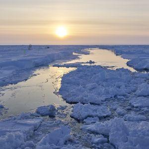 Aurinko taivaanrannassa rakoilevan jään yllä.
