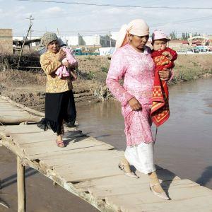 Kaksi uiguurinaista kantaa lapsia sillalla.