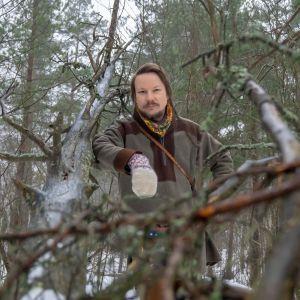 Taiteilija Niillas Holmberg metsässä.