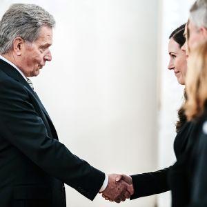 Sauli Niinistö ja Sanna Marin kättelevät.